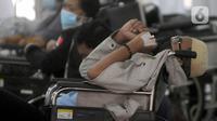 Pasien COVID-19 menunggu di kursi roda untuk mendapatkan kamar perawatan di depan UGD RSUD Cengkareng, Jakarta, Kamis (24/6/2021). Lonjakan kasus virus corona mengakibatkan ruang IGD penuh, pihak rumah sakit lantas mendirikan tenda darurat untuk merawat pasien covid-19. (merdeka.com/Arie Basuki)