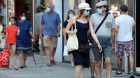 Orang-orang memakai masker saat berjalan di Brussel, Belgia, Rabu (12/8/2020). Penggunaan masker menjadi wajib di tempat umum di Brussel karena kasus Covid-19 naik ke tingkat kewaspadaan yang menempatkan kota itu di antara yang paling parah terkena dampak corona di Eropa. (François WALSCHAERTS/AFP)