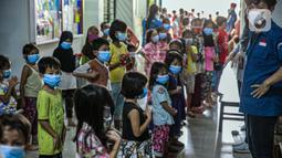 Relawan Forum Anak Jakarta Timur mengajak anak-anak korban banjir bermain di tempat pengungsian di Gedung SD Kampung Melayu 01/02, Kebon Pala, Jakarta, Selasa (9/2/2021). Kegiatan ini untuk mengembalikan semangat anak-anak. (Liputan6.com/Faizal Fanani)
