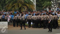 Petugas berusaha menenangkan sopir taksi yang melempar batu saat saat demo di depan Istana Negara, Jakarta, Selasa (22/3). Aksi lempar batu itu pecah saat pengunjuk rasa mendapat ejekan dari pengemudi ojek online. (Liputan6.com/Gempur M Surya)