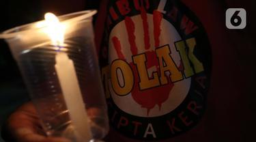 Salah satu peserta aksi unjuk rasa memegang lilin saat doa bersama lintas agama di Kawasan Patung Kuda, Jakarta, Selasa (10/11/2020). Sejumlah massa gabungan dari berbagai organisasi buruh dan mahasiswa berunjuk rasa menolak pengesahan Omnibus Law UU Cipta Kerja. (Liputan6.com/Helmi Fithriansyah)