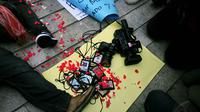 Sejumlah wartawan mengumpulkan ID Card, kamera, dan alat perekam saat berunjuk rasa di Bundaran HI, Jakarta, Jumat (14/11/2014). (Liputan6.com/Johan Tallo)