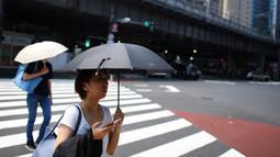 Seorang wanita melindungi dirinya dari matahari dengan payung selama gelombang panas di Tokyo, Jepang (1/8/2019). Selain Tokyo, Kota Tajimi di Perfektur Gifu, Kota Kyoto, dan Kota Hatoyama di Perfektur Saitama juga menjadi wilayah terpanas di Jepang. (AFP Photo/Charly Triballeau)