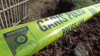 Garis polisi dipasang di lokasi makam yang dibongkar orang tak dikenal di Bekasi. (Bam Sinulingga/Liputan6.com)