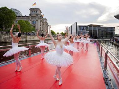 """Penari dari Berlin State Ballet menari """"Swan Lake"""" di atas kapal pesiar selama tur pusat kota saat kapal berlayar di depan gedung Reichstag (kiri), Berlin, Jerman, Kamis (10/6/2021). Pertunjukan diikuti oleh banyak orang di sepanjang rute. (Christoph Soeder/dpa via AP)"""