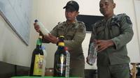 Petugas Satpol PP Kota Cirebon tengah sibuk mendata puluhan botol miras hasil razia. Foto (Liputan6.com / Panji Prayitno)