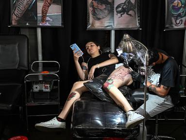 Seorang wanita bermain ponsel saat membuat tato dikakinya selama Expotattoo Colombia 2019 di Medellin, departemen Antioquia (2/6/2019). Para penggila tato antusias untuk mentato tubuhnya di festival tato terbesar di negara tersebut. (AFP Photo/Joaquim Sarmiento)