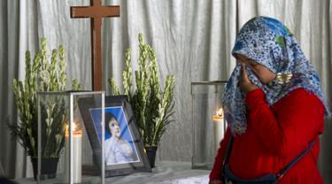 Seorang ibu mengusap air mata di depan peti mati korban bom Surabaya Sri Puji, Surabaya, Jawa Timur, Senin (14/5). Sri Puji menjadi korban meninggal dalam serangan di Gereja Pantekosta. (AFP PHOTO/JUNI KRISWANTO)