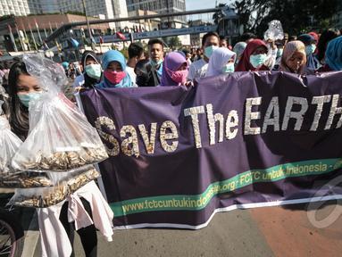 Aktivis Gerakan Muda FCTC melakukan aksi mengumpulkan puntung rokok di kawasan Bundaran HI, Jakarta, Minggu (26/4/2015). Kegiatan tersebut untuk memperingati Hari Bumi. (Liputan6.com/Faial Fanani)