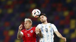 Pemain Argentina, Nicolas Tagliafico, duel udara dengan pemain Chili, Eduardo Vargas, pada Kualifikasi Piala Dunia 2022 Zona Amerika Selatan di Stadion Santiago del Estero, Jumat (4/6/2021). Kedua tim bermain imbang 1-1. (Agustin Marcarian, Pool via AP)
