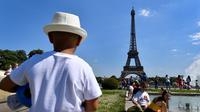 Warga berjemur di samping air mancur di Trocadero Esplanade, dekat Menara Eiffel, Paris (8/5). Seluruh situs di tempat ini dulunya adalah taman tua Palais du Trocadéro, yang ditata oleh Jean-Charles Alphand. (AFP Photo/Gerard Julien)