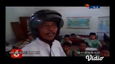Seorang guru di SDN Kepuhkembeng 1 Jombang, Jawa Timur mengenakan helm saat mengajar. Diketahui ternyata bangunan sekolah tersebut sudah rusak parah.