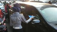 Petugas Sudin Perhubungan Jakarta Selatan memberikan brosur terkait perluasan Ganjil Genap sebagai bentuk sosialisasi terhadap pengguna jalan.