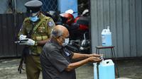 Seorang pemilih membersihkan tangan sebelum memasuki tempat pemungutan suara di Kolombo, Sri Lanka, Rabu (5/8/2020). Sri Lanka menggelar pemilihan parlemen di tengah pandemi COVID-19. (Ishara S. KODIKARA/AFP)