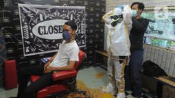 Seorang tukang cukur memakai alat pelindung diri (APD) buatannya sendiri sebelum mencukur pelanggannya di Chemot Barbershop, Ciawi, Bogor, Jawa Barat, Minggu (5/4/2020). (merdeka.com/Arie Basuki)