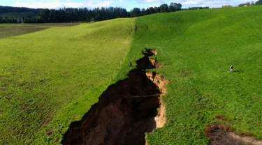 Lubang besar terlihat di peternakan sapi perah dekat Rotorua di Pulau Utara Selandia Baru (2/5). Lubang sedalam empat bus bertingkat dan hampir sepanjang dua lapangan sepakbola telah menarik perhatian para ahli gunung berapi Selandia Baru. (AFP Phot/TVNZ)
