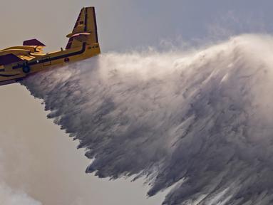 Sebuah pesawat Royal Moroccan Air Force Canadair memadamkan kebakaran hutan di wilayah Chefchaouen, Maroko, 17 Agustus 2021. Petugas pemadam kebakaran Maroko berjuang untuk memadamkan dua kebakaran hutan saat negara tersebut dilanda gelombang panas. (FADEL SENNA/AFP)