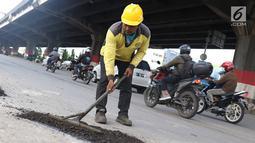 Petugas menambal lubang pada jalan yang rusak di kawasan Jatinegara, Jakarta, Kamis (7/2). Musim hujan yang mengguyur Jakarta selama beberapa waktu terakhir meninggalkan kerusakan pada sejumlah ruas jalan di Ibukota. (Liputan6.com/Immanuel Antonius)