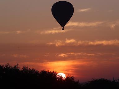 Sebuah balon udara terbang di atas kuil tua selama matahari terbit di Bagan, distrik Nyaung U, Myanmar tengah (16/12). Di Bagan, ada tiga balon yang bisa memuat delapan orang dan dua balon yang bisa memuat dua belas orang. (AP Photo/Aung Shine Oo)