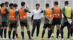 Pelatih Timnas Indonesia U-22, Indra Sjafri, memberikan instruksi kepada para pemainnya saat latihan di Stadion Madya, Jakarta, Selasa (15/1). Latihan ini merupakan persiapan jelang Piala AFF U-22. (Bola.com/Yoppy Renato)