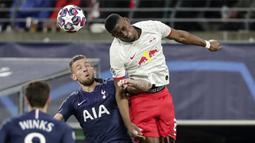 Bek Red Bull Leipzig, Nordi Mukiele berebut bola dengan bek Tottenham Hotspur, Toby Alderweireld pada pertandingan leg kedua babak 16 besar Liga Champions di di Red Bull Arena, Jerman (10/3/2020). RB Leipzig menang telak atas Tottenham 3-0. (AP Photo/Michael Sohn)