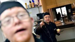 """Asisten memasak dengan down syndrome beraktivtas menyiapkan makanan di dapur restoran """"Le Reflet"""" di Nantes, Prancis Barat, 9 Februari 2017. Lelievre (26), mempekerjakan sejumlah karyawan yang memiliki down syndrome di restorannya. (LOIC VENANCE/AFP)"""