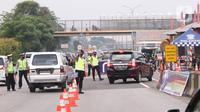 Petugas gabungan mengarahkan pengendara mobil untuk putar balik saat akan memasuki wilayah Jakarta di Gerbang Tol Cikupa, Tangerang, Rabu (27/5/2020). Kendaraan yang menuju Jakarta wajib menunjukkan Surat Izin Keluar atau Masuk (SIKM) untuk menekan penyebaran Covid-19. (Liputan6.com/Angga Yuniar)