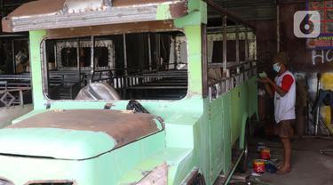 Pekerja menyelesaikan pembuatan mobil wisata Odong-Odong di bengkel perakitan milik Didik Hermawan di Jurangmangu, Tangerang Selatan, Sabtu (27/2/2021). Pada masa pandemi Covid-19, permintaan mobil odong-odong tetap stabil melalui transaksi pasar online. (Liputan6.com/Angga Yuniar)
