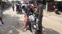 Petugas yang melakukan penjagaan ketat di check point  tidak segan-segan menindak pelanggar PSBB Karawang. (Foto: Liputan6.com/Abramena)