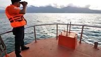 Anggota Basarnas memantau pencarian serpihan pesawat AirAsia QZ8501 di Teluk Palu. (Liputan6.com/Dio Pratama)