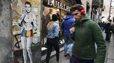 Sejumlah warga melintasi mural dengan gambar bintang Juventus, Cristiano Ronaldo, yang terdapat di Milan, Senin (19/3). Mural berjudul Cristiano's Secret ini karya seniman Italia, TvBoy. (AFP/Miguel Medina)