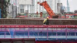 Kendaraan melintas di bawah pembangunan proyek Light Rail Transit (LRT) Jabodebek fase I di kawasan Cawang, Jakarta, Senin (14/1). Progres konstruksi stasiun LRT Cawang, Jakarta Timur sudah mencapai 62,2 persen. (Liputan6.com/Faizal Fanani)