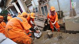 Petugas PPSU Kelurahan Kampung Melayu Siti Hajar bersama rekan-rekannya membersihkan sisa lumpur akibat banjir yang melanda Kebon Pala, Jakarta, Kamis (25/4). (Liputan6.com/Herman Zakharia)