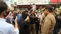 Pedagang di PGC Kota Cirebon menghalau petugas Gugus Tugas Percepatan Penanganan Covid-19 saat sedang memberi imbauan untuk tidak berjualan. Foto (Liputan6.com / Panji Prayitno)