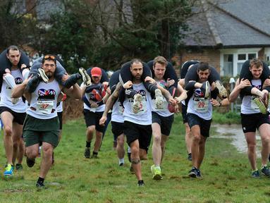 Para peserta bersaing dalam Lomba Lari Gendong Istri di The Nower, Dorking, Inggris, Minggu (3/3). Para suami harus menggendong istri mereka dari garis start hingga finish. (Gareth Fuller/PA via AP)