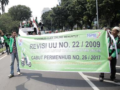 Massa dari pengemudi ojek online membentangkan spanduk sambil bergerak menuju Istana Negara, Jakarta, Senin (15/5). Mereka menuntut agar pemerintah segera merevisi UU No 22 Tahun 2009 tentang Lalu Lintas dan Angkutan Jalan. (Liputan6.com/Faizal Fanani)