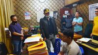 Tersangka penganiaya pengemudi ojek online ketika berada di ruang pemeriksaan Polresta Pekanbaru. (Liputan6.com/M Syukur)