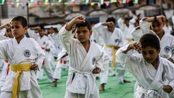 Anak-anak Palestina menunjukkan keterampilannya selama upacara promosi Karate di sebuah pusat olahraga di kamp Rafah untuk pengungsi Palestina di Jalur Gaza selatan (20/9/2019). (AFP Photo/Said Khatib)