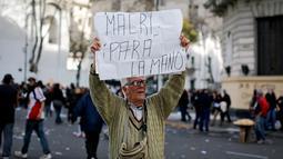 """Pria paruh baya membawa papan berisi """"Macri, hentikan!"""" dalam bahasa Spanyol saat demonstrasi di Plaza de Mayo, Buenos Aires, Argentina, Selasa (22/8). Macri berusaha menurunkan upah para buruh demi menghasilkan Investasi lebih. (Victor R. Caivano/AP)"""