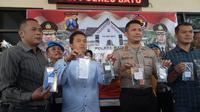 Polres Batu, Jawa Timur, menunjukkan barang bukti berupa buku tabungan sampai rekap transfer uang (Zainul Arifin/Liputan6.com)