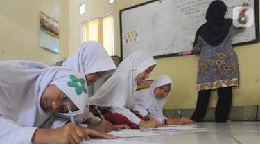 Sejumlah siswa kelas VI  Madrasah Ibtidaiyah Mathlaul Anwar Ciangsana belajar di lantai tanpa meja dan kursi pada bangunan majelis taklim, Tenjolaya, Kabupaten Bogor, Selasa(22/10/2019).  Kegiatan  dilakukan karena dua dari lima ruang kelas yang ada sudah rusak dan lapuk. (merdeka.com/Arie Basuki)