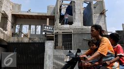Warga saat melintasi Gereja Kristen Protestan Indonesia (GKPI) saat di bongkar di Jatinegara, Jakarta Timur, Sabtu (25/7/2015). Gereja ini terpaksa dibongkar karena tidak mempunyai Ijin Mendirikan Bangunan (IMB). (Liputan6.com/Johan Tallo)
