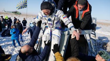 Tim penyelamat antariksa Rusia membantu kosmonot Rusia Sergey Ryazanskiy sesaat setelah pendaratan kapsul Soyuz MS-05 di Kazakhstan (14/12). (AP/ Dmitri Lovetsky/Pool)