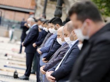 Warga yang mengenakan masker mengikuti salat Jumat, dengan menjaga jarak di depan sebuah masjid di Ankara, 29 Mei 2020. Masjid-masjid di seluruh Turki pada Jumat (29/5) kembali dibuka, sebagai bagian proses normalisasi di tengah melambatnya penyebaran COVID-19 di negara itu. (Xinhua/Mustafa Kaya)