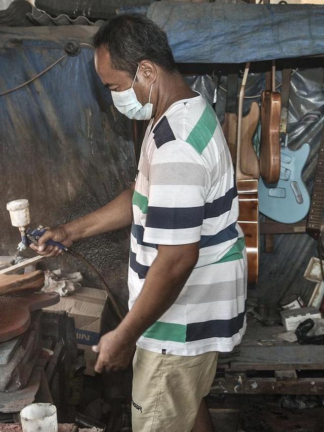 Soedarmadi yang akrab disapa Bone menyelesaikan pembuatan gitar di workshop Bone's Costum Guitar, Jakarta, Rabu (10/3/2021). Untuk mencukupi kebutuhan sehari-hari, ayah dari 4 anak ini mencari sampingan dengan membuka ternak cupang hias sembari menunggu pelanggan gitar. (merdeka.com/Iqbal S Nugroho)