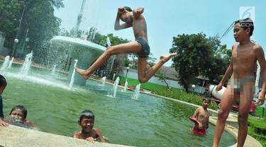 Seorang anak melompat di bundaran air mancur Jalan Teuku Umar, Jakarta Pusat, Sabtu (23/9). Cuaca panas ibu kota memaksa anak-anak menceburkan diri di kolam untuk menyejukkan badan. (Liputan6.com/Helmi Afandi)