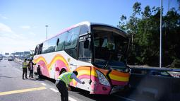Polisi mengecek tempat kejadian kecelakaan bus dan taksi di Hong Kong (30/11). Bus tersebut dalam perjalanan ke bandara Hong Kong bertabrakan dengan taksi, kata polisi, dengan penumpang dilaporkan terlempar dari jendela bus. (AFP Photo/Anthony Wallace)