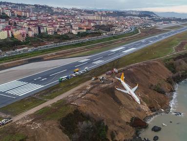 Sebuah pesawat dari maskapai Pegasus Airlines nyaris terperosok ke dalam laut di bandara Trabzon, Turki, Minggu (14/1). Peristiwa tersebut terjadi setelah pesawat mendarat dan  tergelincir dari landasan pacu. (DOGAN NEWS AGENCY/AFP)