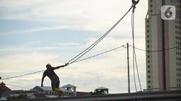 Pekerja menyelesaikan pembangunan Kampung Susun Akuarium di kawasan Penjaringan, Jakarta Utara,  Kamis (07/02/2021).  Pembangunan yang bersumber dari APBD Provinsi DKI Jakarta juga berasal dari dana kewajiban pengembang senilai Rp 62 miliar. (Liputan6.com/Fery Pradolo)