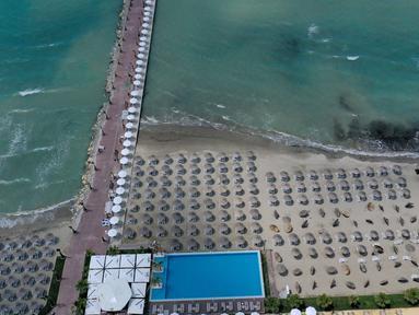 Foto udara pada 1 Juni 2020 menunjukkan payung-payung jerami di sebuah pantai di Qerret, dekat kota Kavaja, Albania. Rencananya pada 6 Juni mendatang, semua pantai umum akan dibuka untuk wisatawan setelah Albania menerapkan langkah-langkah pelonggaran pencegahan virus corona. (SHKULLAKU / AFP)